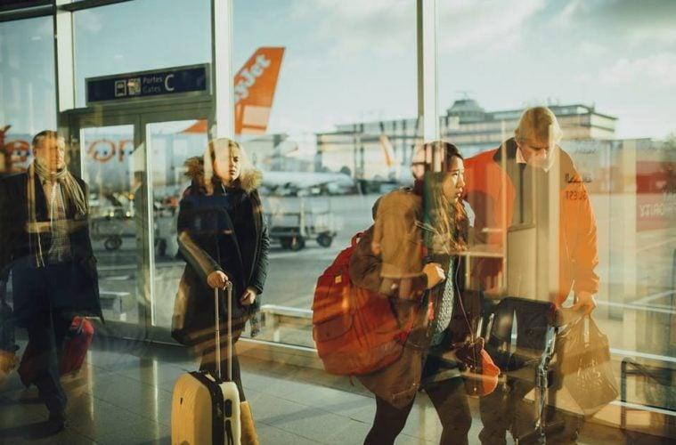 Хора се разминават на летищен терминал.