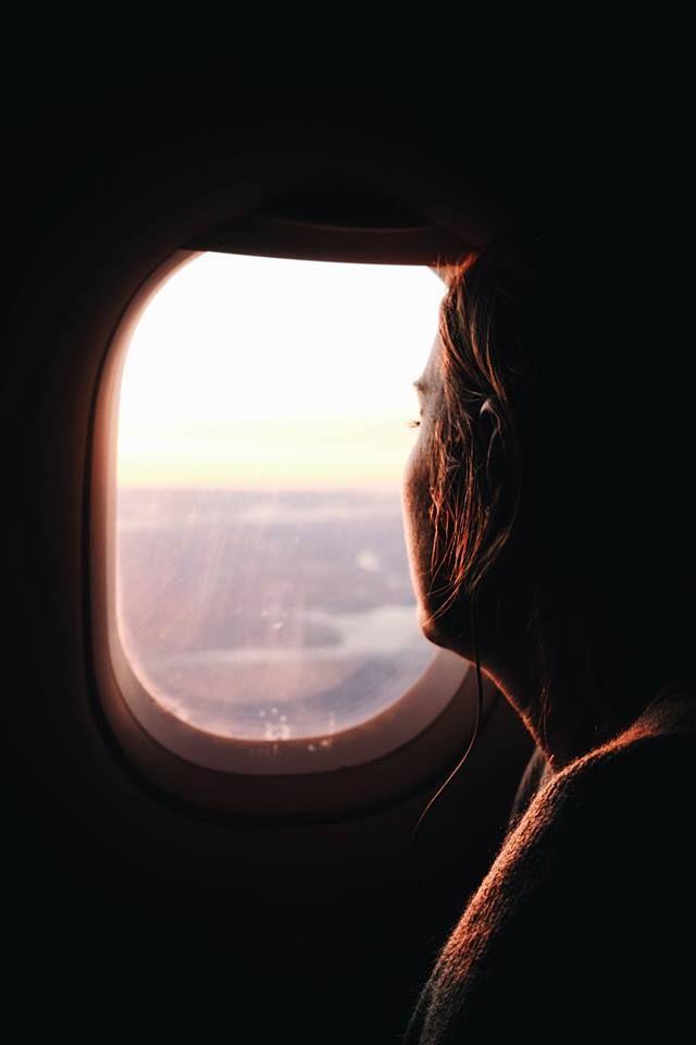 Пътник се взира през прозорец, докато лети със самолет.