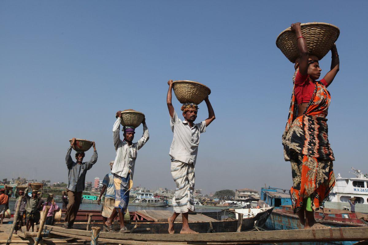 Работници пренасят пясък в Бангладеш