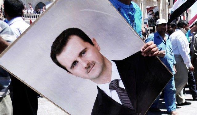 Демонстрант държи портрет на сирийския президент Башар Асад