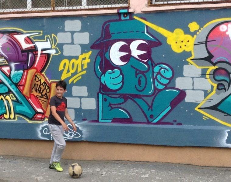 Стена с графит и момче с футболна топка пред нея